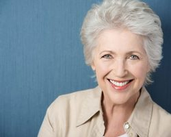 A woman smiling after her dental implant restoration at Alan J. Binstock DDS Family and Cosmetic Dentistry